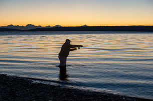 A silhouette of a fly fisherman casting at sunrise for searun coastal cutthroat trout on a beach onの写真素材 [FYI02265989]