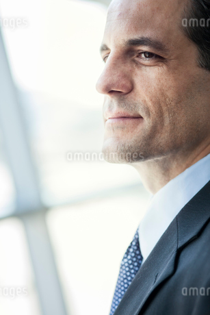 Closeup of a Caucasian businessman looking out the widow of a conference centre lobby.の写真素材 [FYI02265993]