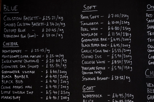 Close up of blackboard with handwritten list of cheese products in a delicatessen.の写真素材 [FYI02266005]