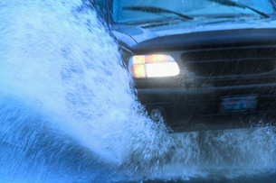Closeup of the front end of a car going through a mud puddle.の写真素材 [FYI02266010]