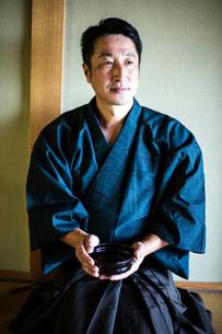 Japanese man wearing kimono kneeling on floor, holding tea bowl during tea ceremony.の写真素材 [FYI02266013]