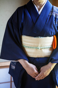 Close up of Japanese woman wearing traditional bright blue kimono with cream coloured obi kneeling oの写真素材 [FYI02266014]