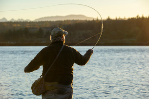 A view from behind of a fly fisherman casting for salmon and searun coastal cutthroat trout from a sの写真素材 [FYI02266019]