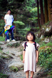 Japanese girl wearing pale pink sun dress and carrying backpack standing in a forest, man in the bacの写真素材 [FYI02266021]