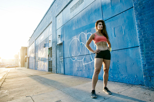 Female athlete standing on sidewalk next to blue building covered in graffiti.の写真素材 [FYI02266022]