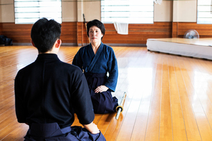 Female and male Japanese Kendo fighters kneeling opposite each other on wooden floor.の写真素材 [FYI02266024]