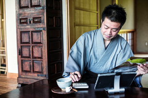 Japanese man wearing kimono sitting on floor in traditional Japanese house, using calculator and digの写真素材 [FYI02266034]