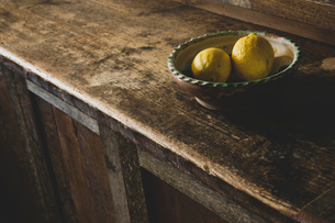 High angle close up of two lemons in earthenware bowl on vintage wooden kitchen cupboard.の写真素材 [FYI02266035]