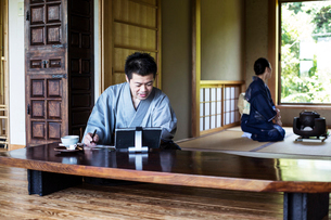 Japanese man wearing kimono sitting on floor in traditional Japanese house, looking at digital tableの写真素材 [FYI02266060]