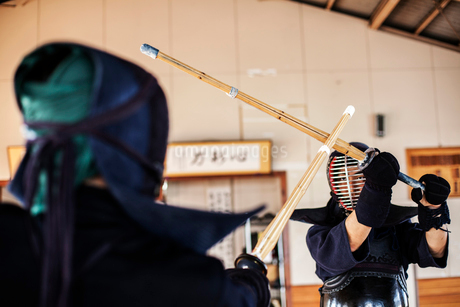 Two Japanese Kendo fighters wearing Kendo masks practicing with wood sword in gym.の写真素材 [FYI02266063]
