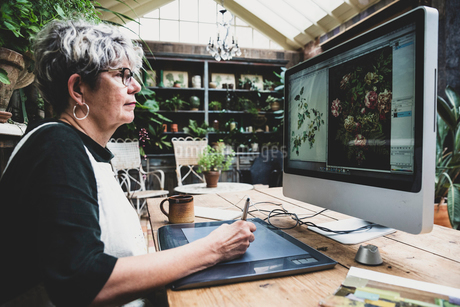 Senior woman wearing glasses, black top and white apron sitting at a wooden table, working on desktoの写真素材 [FYI02266072]
