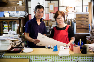 A man and woman, partners in a traditional business,  behind a counter in a shop, displays of traditの写真素材 [FYI02266073]