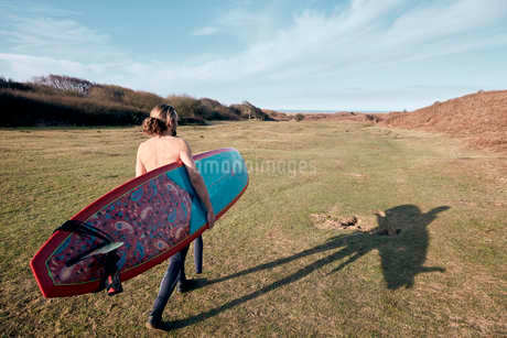 Man walking on a path in the sand dunes towards sea with a surf boardの写真素材 [FYI02266078]