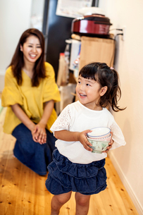 Smiling Japanese woman kneeling in a corridor behind young girl carrying stack of bowls.の写真素材 [FYI02266079]