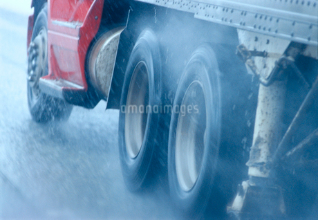 Partial view of large commercial truck driving in hazardous conditions of snow and rain on a freewayの写真素材 [FYI02266084]