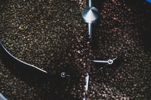 High angle close up of freshly roasted coffee beans in coffee roaster.の写真素材 [FYI02266087]