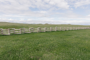Concrete snow barrier, angled fencing across a verdant mountain meadow.の写真素材 [FYI02266089]
