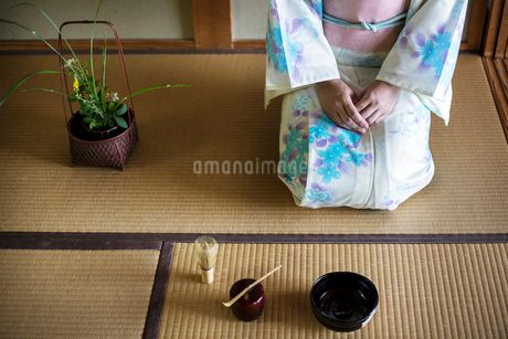 Japanese woman wearing traditional white kimono with blue floral pattern kneeling on tatami mat in fの写真素材 [FYI02266104]