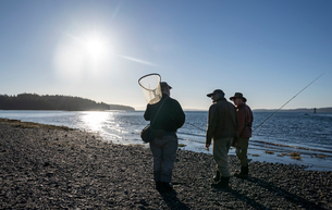 Two fly fisherman talk with their guide about new techniques while fly fishing for searun coastal cuの写真素材 [FYI02266105]