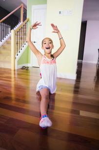 Happy girl doing splits in homeの写真素材 [FYI02266114]