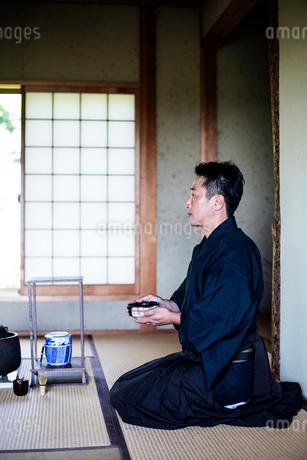 Japanese man wearing traditional kimono kneeling on floor, holding tea bowl, during tea ceremony.の写真素材 [FYI02266122]