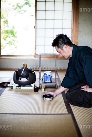 Japanese man wearing traditional kimono kneeling on floor, holding tea bowl, during tea ceremony.の写真素材 [FYI02266123]