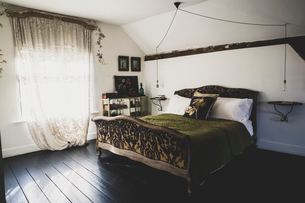Interior view of attic bedroom with dark wooden floor and white walls, antique French double bed witの写真素材 [FYI02266126]