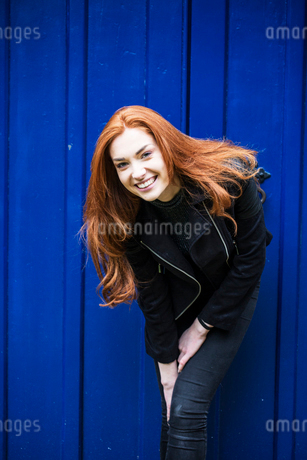 Portrait of smiling young woman with long red hair in front of bright blue door.の写真素材 [FYI02266134]