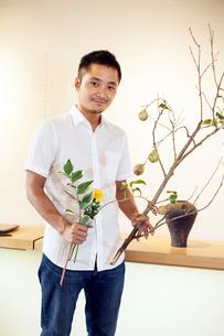Japanese man working in a flower gallery, working on Ikebana arrangement.の写真素材 [FYI02266136]