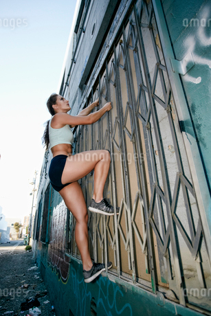 Female athlete climbing up metal window shutter of industrial building.の写真素材 [FYI02266138]