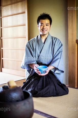 Japanese man wearing traditional kimono kneeling on floor, holding blue tea bowl during tea ceremonyの写真素材 [FYI02266145]