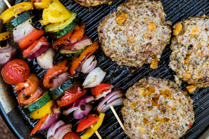 Food on a barbeque, vegetable kebabs and home made burgers, cooking outdoors.の写真素材 [FYI02266146]