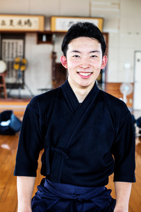 Male Japanese Kendo fighter standing in a gym, smiling at camera.の写真素材 [FYI02266148]
