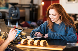 Smiling young woman with long red hair standing at a counter in a restaurant, paying her bill.の写真素材 [FYI02266155]