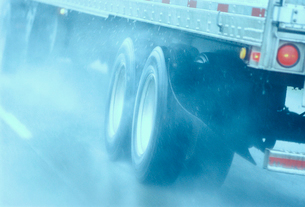 Partial view of large commercial truck driving in hazardous conditions of snow and rain on a freewayの写真素材 [FYI02266160]