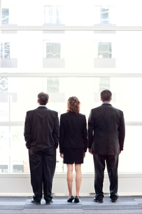 Rear view of group of three business people looking out the window of a conference centre lobby.の写真素材 [FYI02266168]