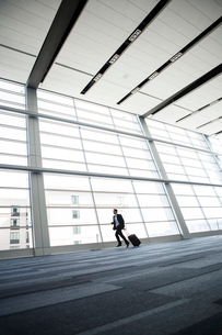 Businessman running past a window in the lobby of a conference centre.の写真素材 [FYI02266170]