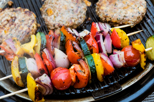 Food on a barbeque, vegetable kebabs and home made burgers, cooking outdoors.の写真素材 [FYI02266171]