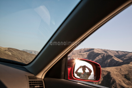 A person looking through binoculars reflected in the side mirror of a car at a rest stop.の写真素材 [FYI02266172]