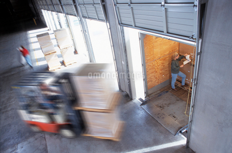 Employees loading cardboard boxes of products into truck trailers in a distribution warehouse loadinの写真素材 [FYI02266177]