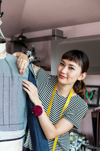 Japanese female fashion designer working on a garment on a dressmaker's model in a studio.の写真素材 [FYI02266186]