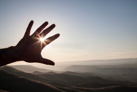 A silhouette of a person's hand in the sun with a landscape of eastern Washington State, USA in theの写真素材 [FYI02266188]