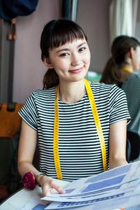 Japanese female fashion designer working in her studio, smiling at camera.の写真素材 [FYI02266203]