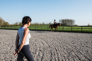 Woman trainer watching a teenage girl riding on a bay brown horse in paddock.の写真素材 [FYI02266204]