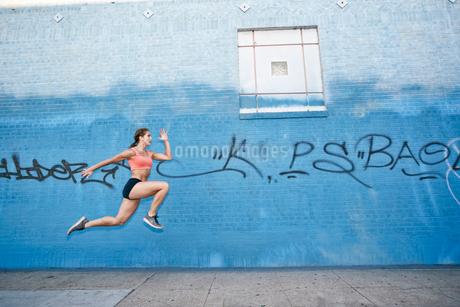 Female athlete running along sidewalk past blue building covered in graffiti.の写真素材 [FYI02266205]