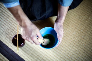 High angle close up of Japanese man wearing traditional kimono kneeling on floor using bamboo whiskの写真素材 [FYI02266206]