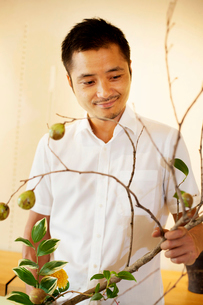 Japanese man working in a flower gallery, working on Ikebana arrangement.の写真素材 [FYI02266212]