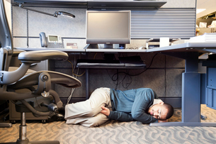 A Black man taking a nap under his desk in a corporate officeの写真素材 [FYI02266217]
