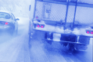 Partial view of large commercial truck driving in hazardous conditions of snow and rain on a freewayの写真素材 [FYI02266227]