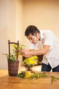 Japanese man working in a flower gallery, working on Ikebana arrangement.の写真素材 [FYI02266229]